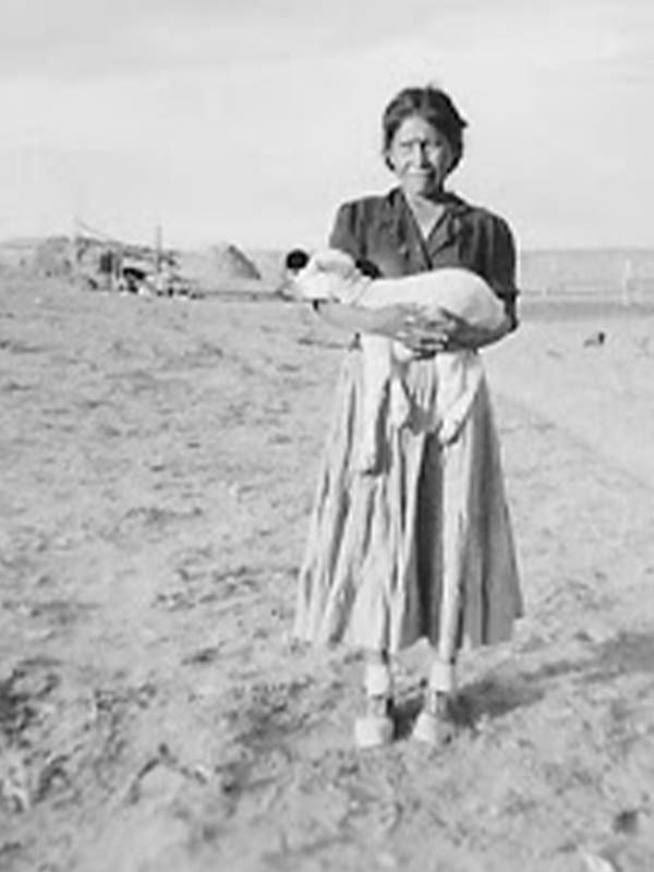 Old photograph of a Navajo Woman standing outsider her home holding a baby lamb, tribal elders, COVID-19, Next Avenue