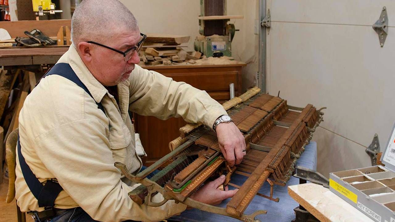 Man at workbench fixing a discarded piano, pianos, restoration, Next Avenue