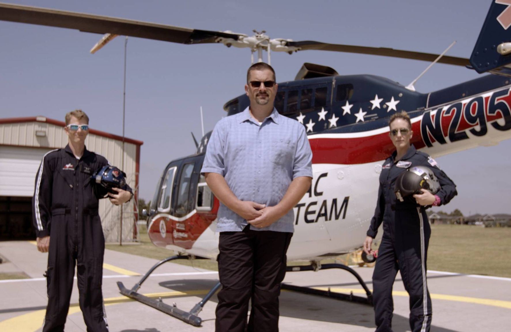 Three men standing on a helicopter tarmac with a helicopter behind them. The man in the center is wearing a blue shirt and sunglasses. The men to either side are in uniform.