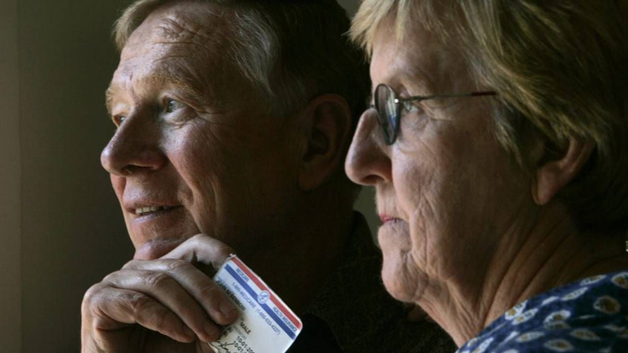 Older couple looking out window holding a Medicare card