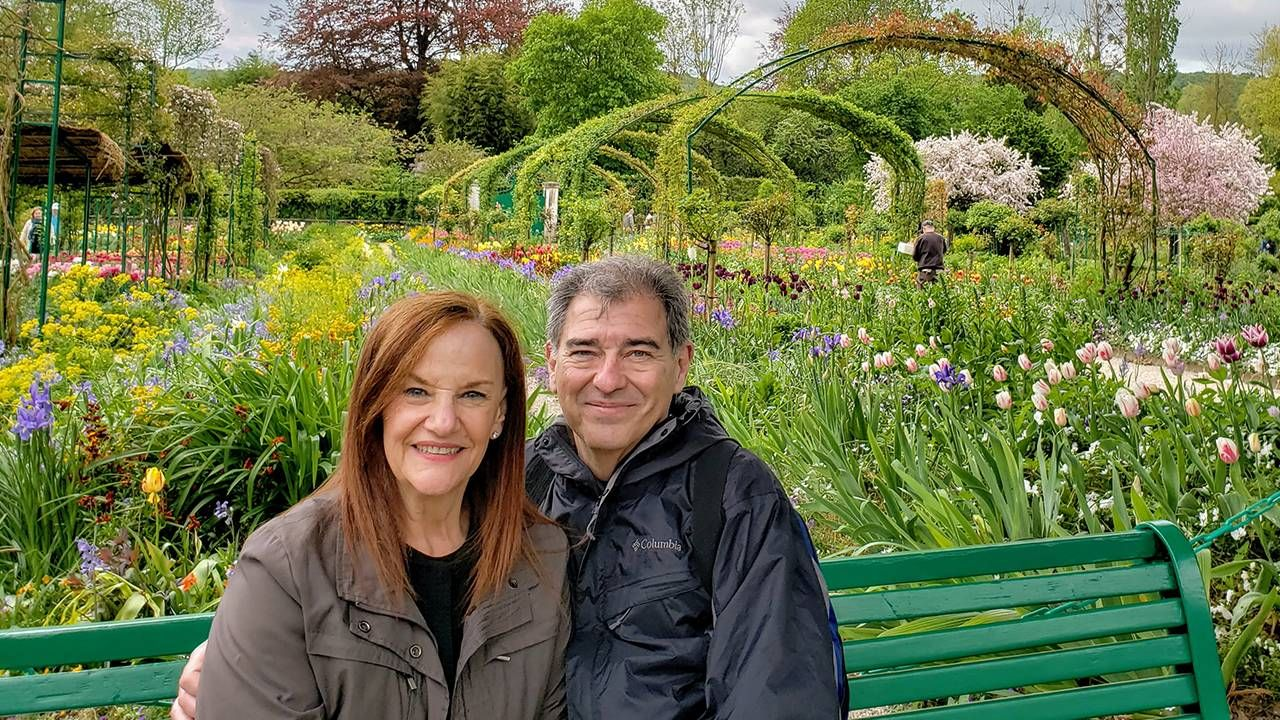 Couple sitting on a bench outside in a spring garden, bucket list, travel, Next Avenue