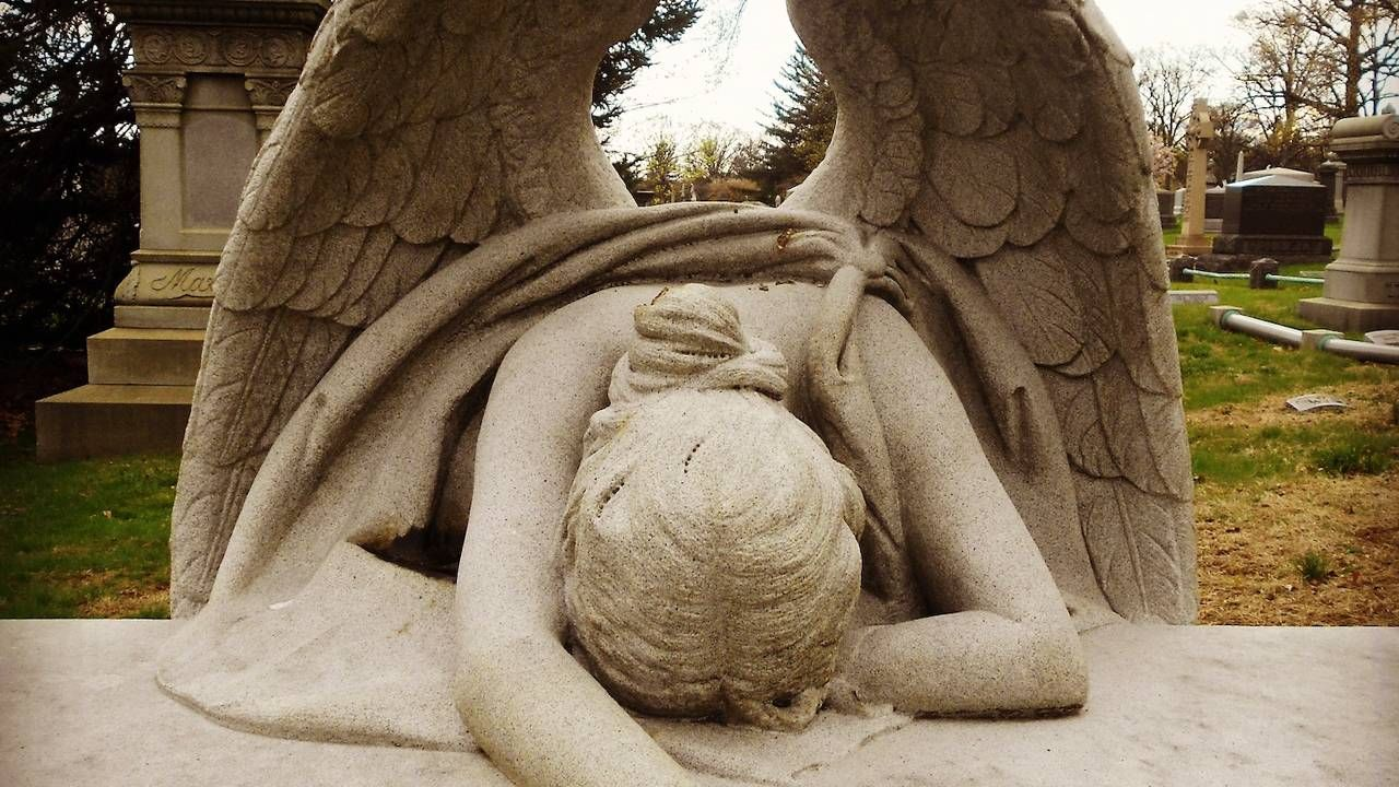 An angel statue laying her head down at a cemetery, grief, funerals, Next Avenue