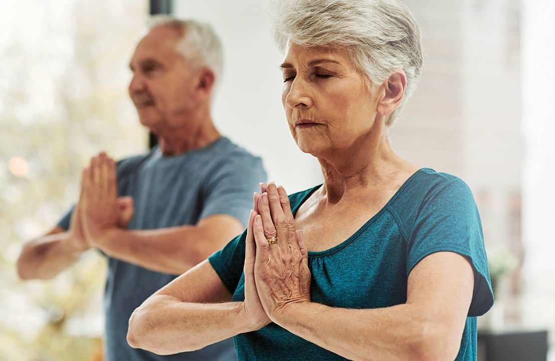 Older couple doing yoga at home, aging, Next Avenue