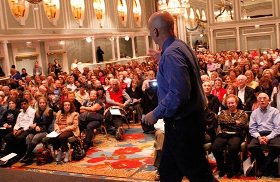 Man walking on stage in front of crowd, adult education, business, Next Avenue