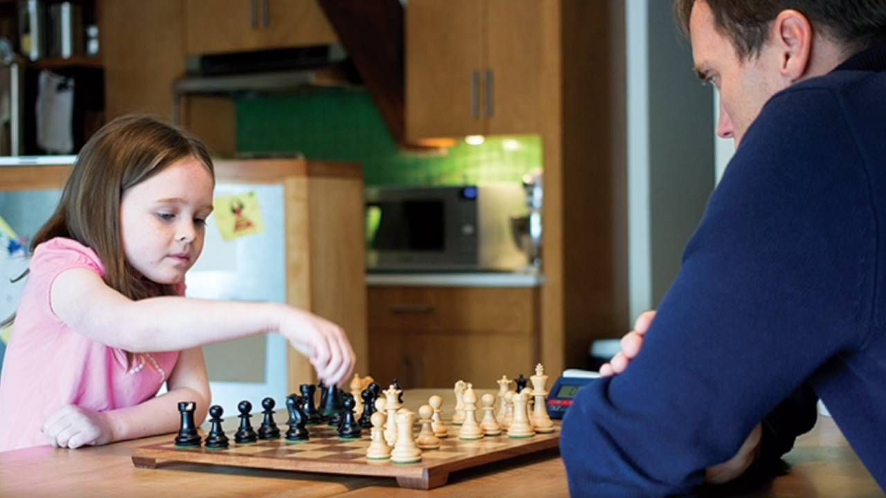 Father and daughter playing chess at home, beginners, lifelong learning, Next Avenue
