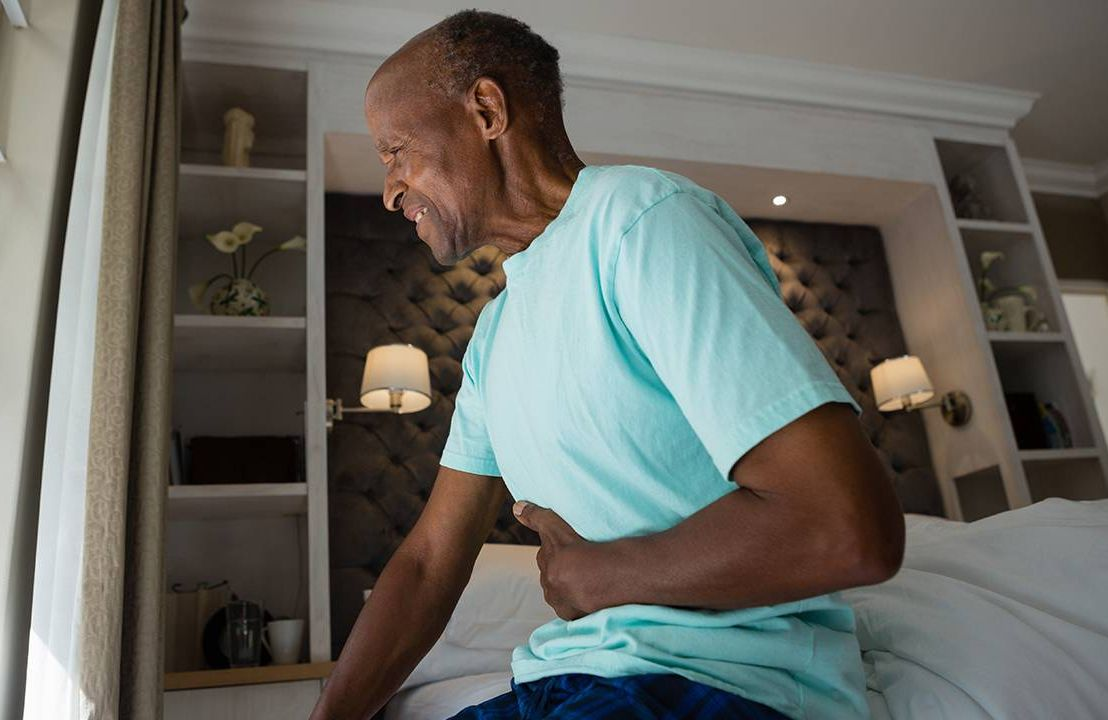 Older man in bed with hand on his stomach, Next Avenue