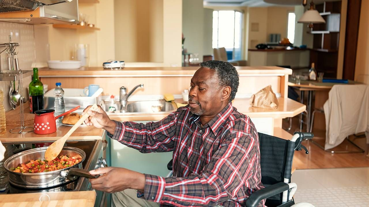 Older man in wheelchair cooking dinner, caregivers, family, COVID-19, Next Avenue