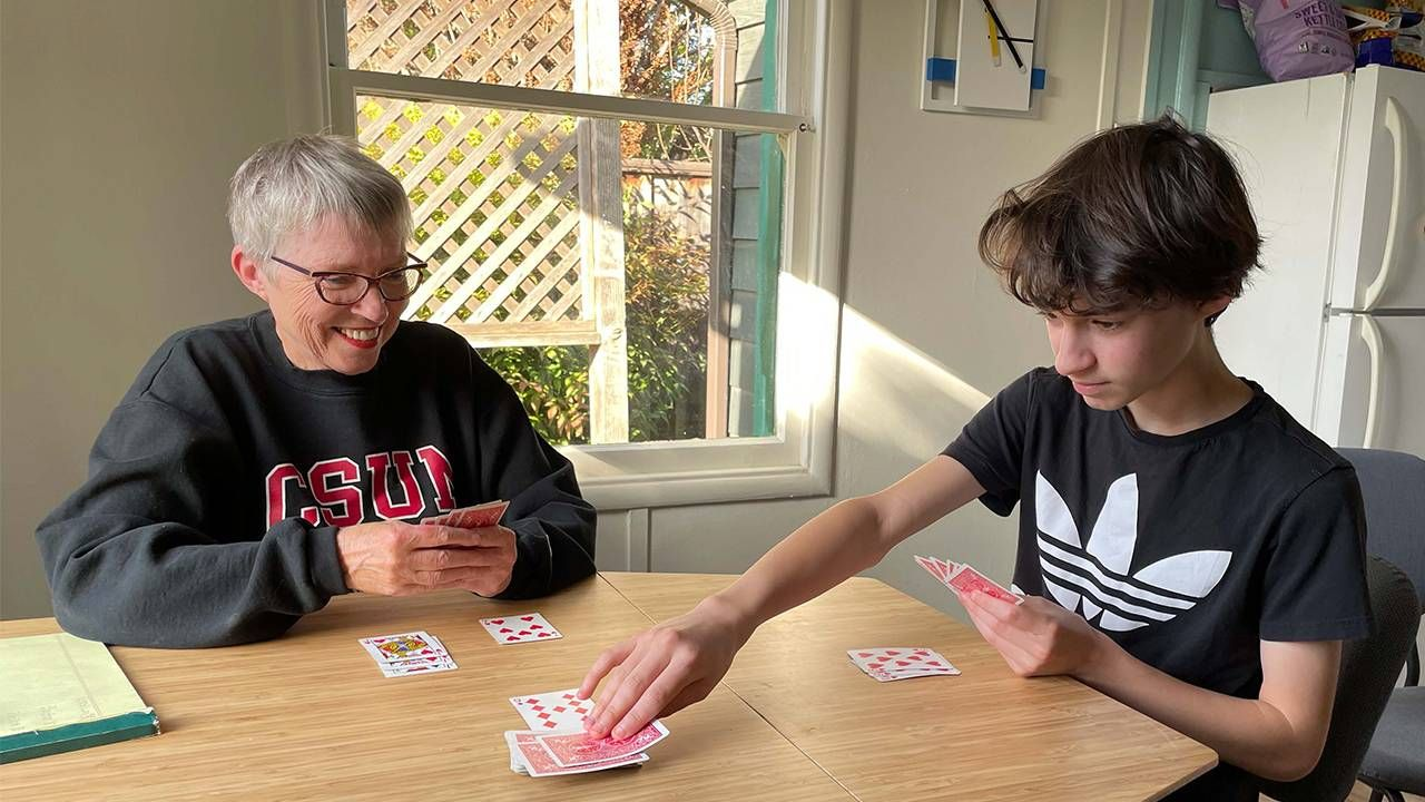 Grandparents and grandson playing cards at the dining table, multigenerational living, Next Avenue