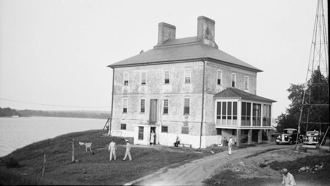 Old photograph of a group home on the water with people outside, history, Next Avenue
