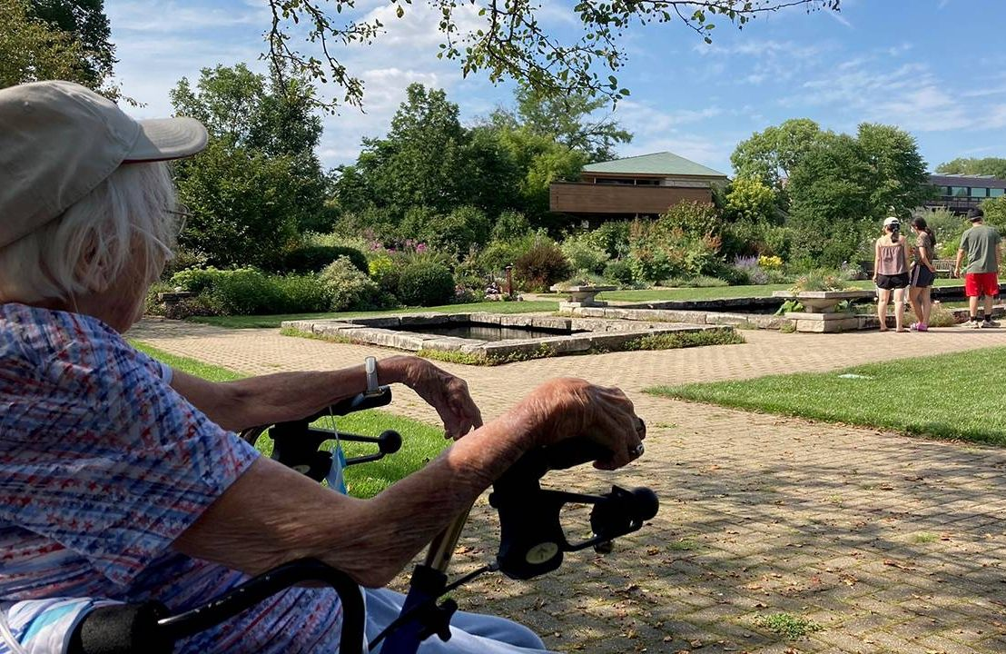 Older woman in wheelchair using oxygen outside in a garden, nature, Next Avenue