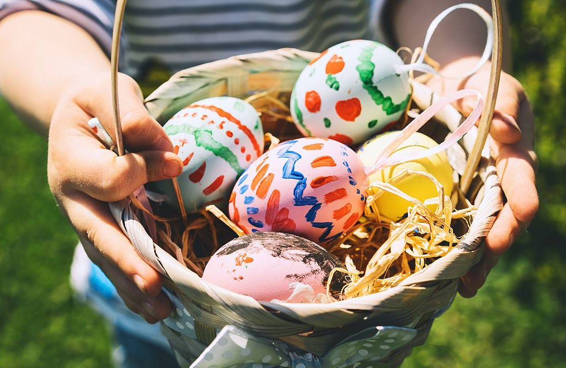Close up of a child holding an easter basket with colorful painted eggs, Easter eggs, hunt, Next Avenue