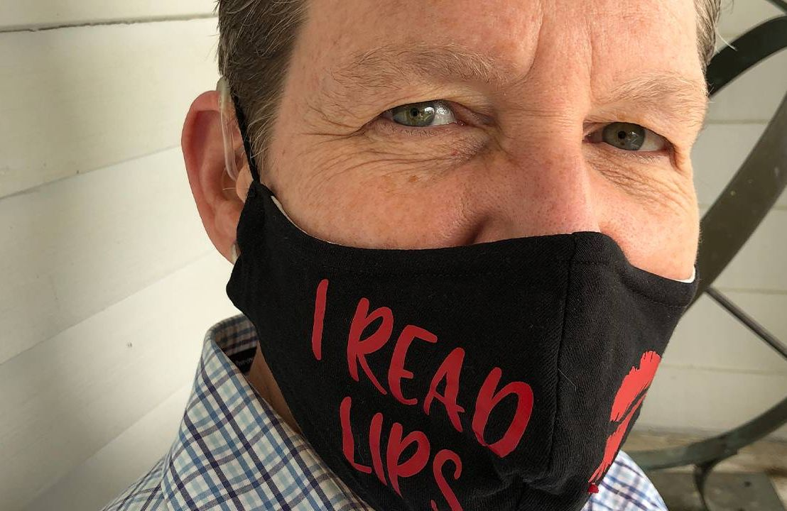 """Close up of a middle aged woman wearing hearing aids and a face mask that says, """"I read lips"""", lip readers, Next Avenue"""