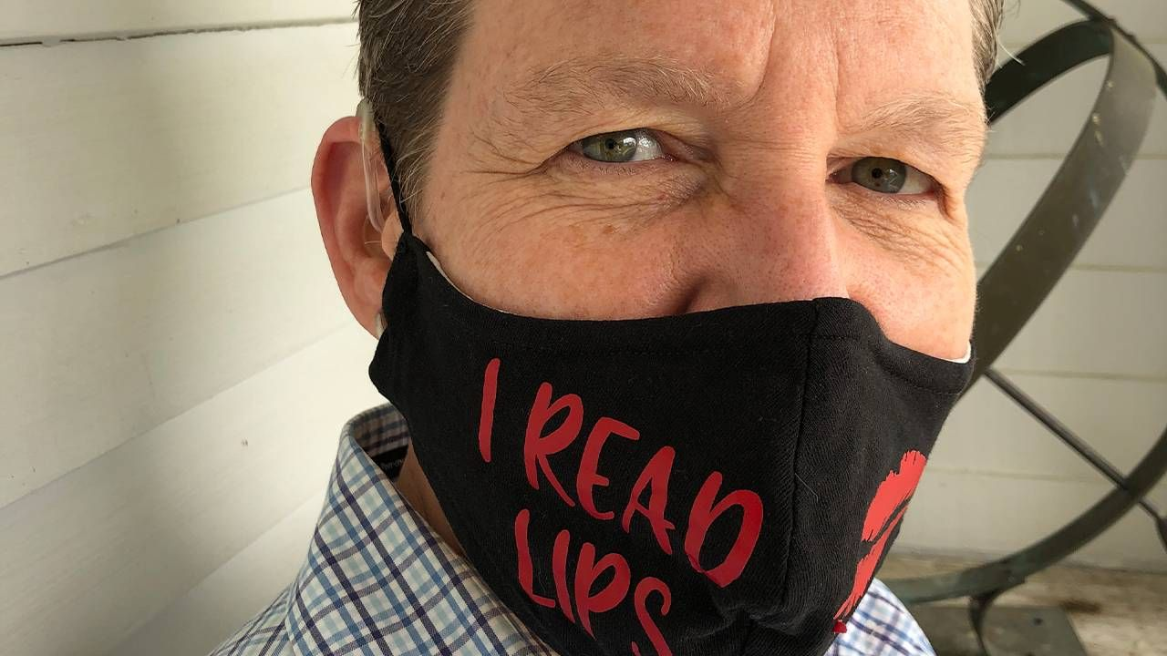 "Close up of a middle aged woman wearing hearing aids and a face mask that says, ""I read lips"", lip readers, Next Avenue"