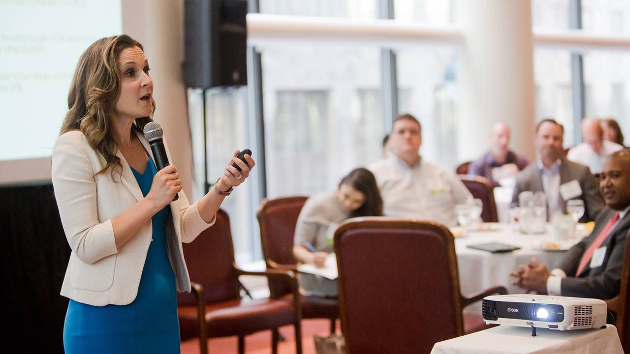 Woman speaking in front of a crowd at conference, career, work, Next Avenue