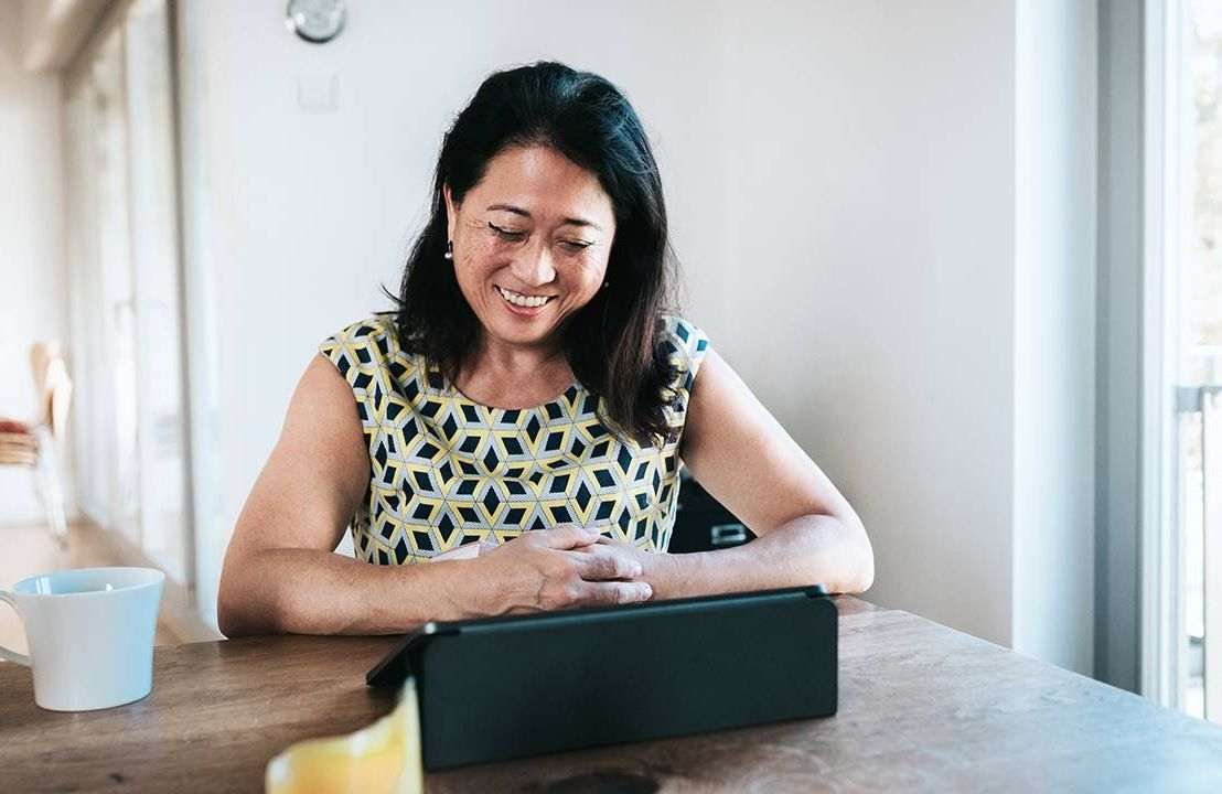 Woman sitting at table on a virtual job interview, career, Next Avenue