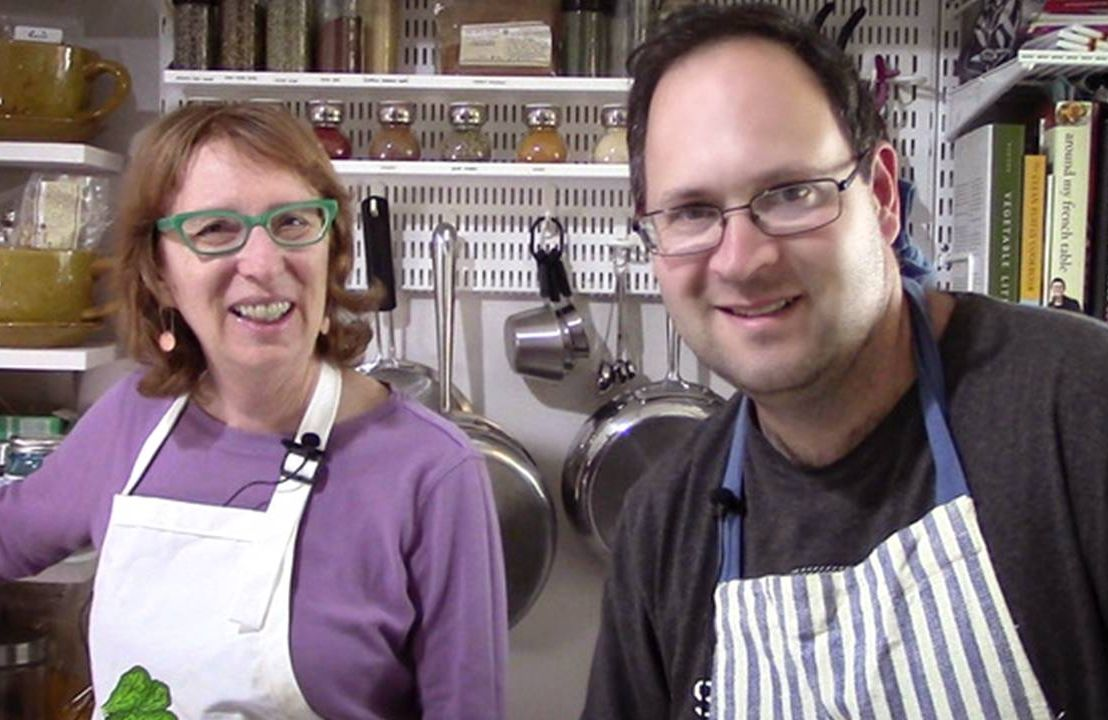 Mother and son wearing aprons cooking together in kitchen, Next Avenue