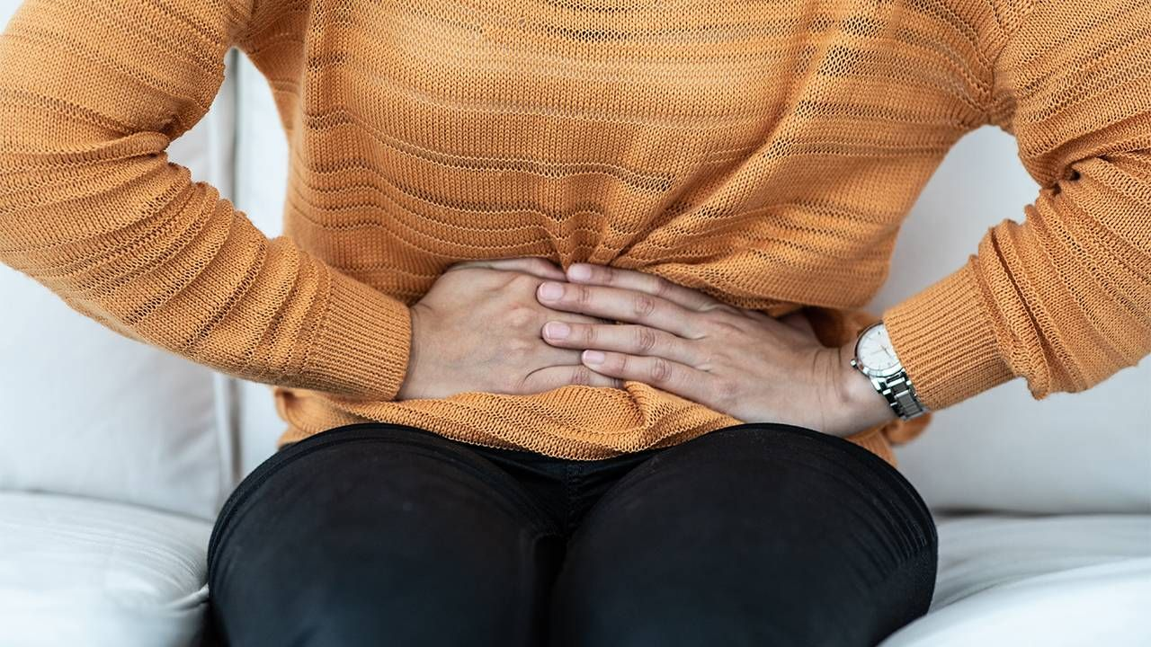 Closeup of a woman holding her bladder in pain sitting on couch, UTI, Next Avenue