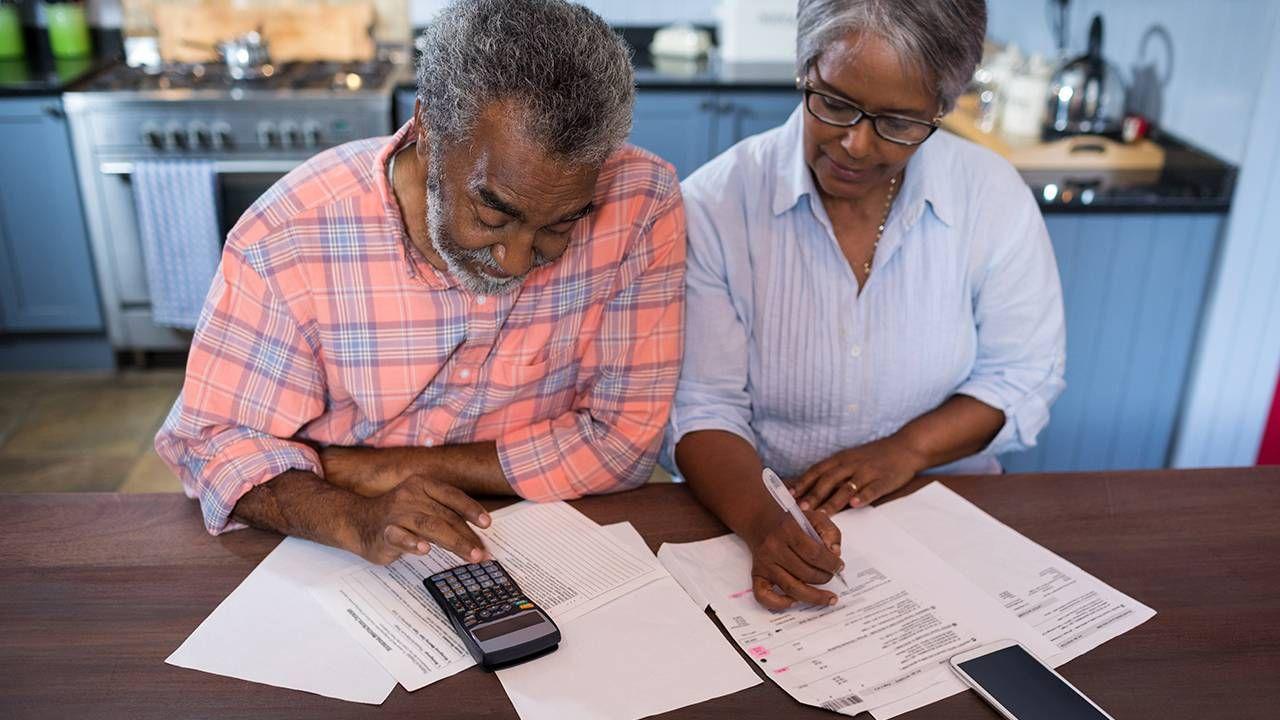 Older couple sitting in kitchen calculating finances, money, Next Avenue
