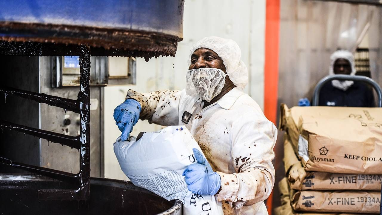 Factory worker mixing ingredients wearing protective gear, jobs, Next Avenue