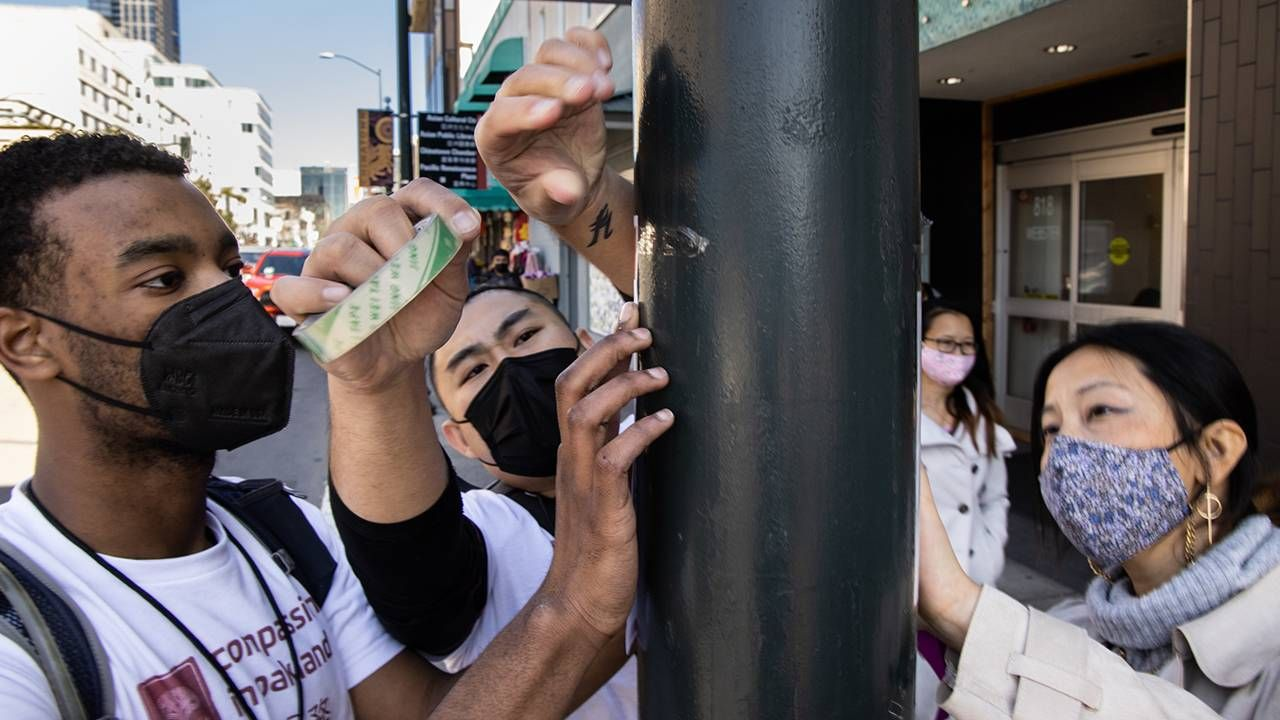 Three young people tape poster to light pole, hate crimes, activism, Next Avenue