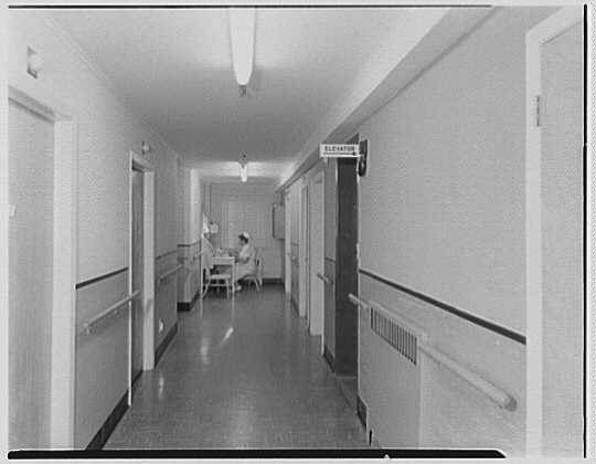 hallway interior with nurse sitting at desk, history, Next Avenue, history of nusring homes