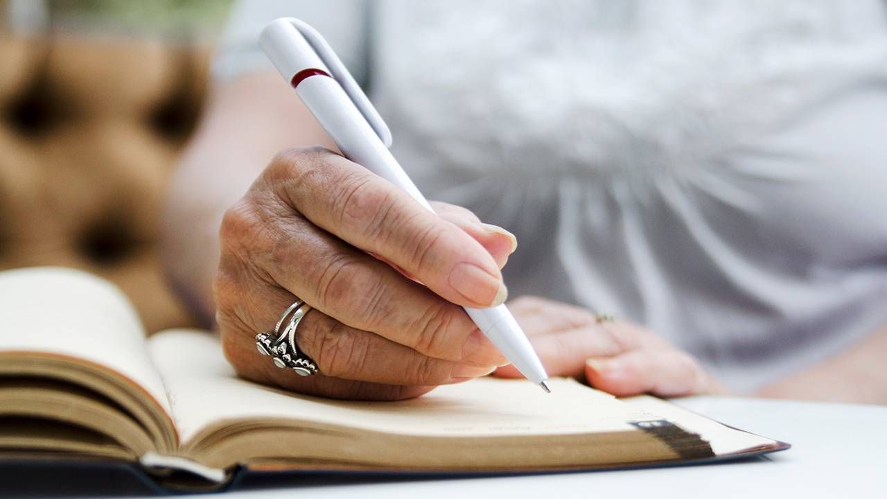 Close up of a woman wearing a silver ring writing in a journal, radiate, positivity, Next Avenue