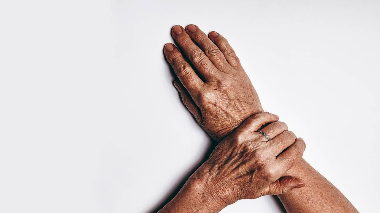 Close up of a middle aged person's hands with some skin spots. Next Avenue