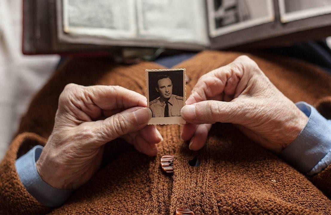 An widow holding an old photo of her late husband. Widows, widowers, estate planning, Next Avenue