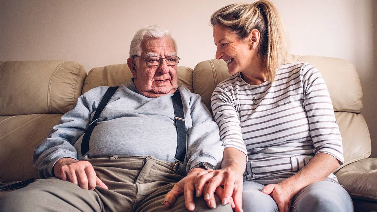 An older man sitting on the couch with his adult daughter. Advance care, Next Avenue