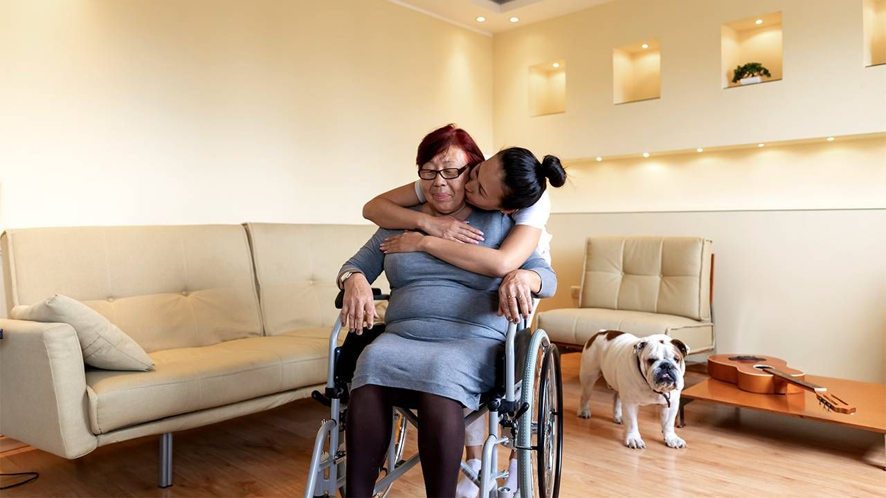 Older woman in wheelchair being hugged by her caregiving daughter, caregiver, caregivers, financial strain, Next Avenue