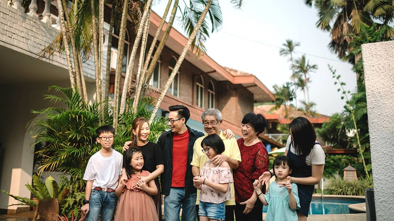 A multigenerational family stands outside in front of the grandparent's house. Estate tax, inheritance, Next Avenue