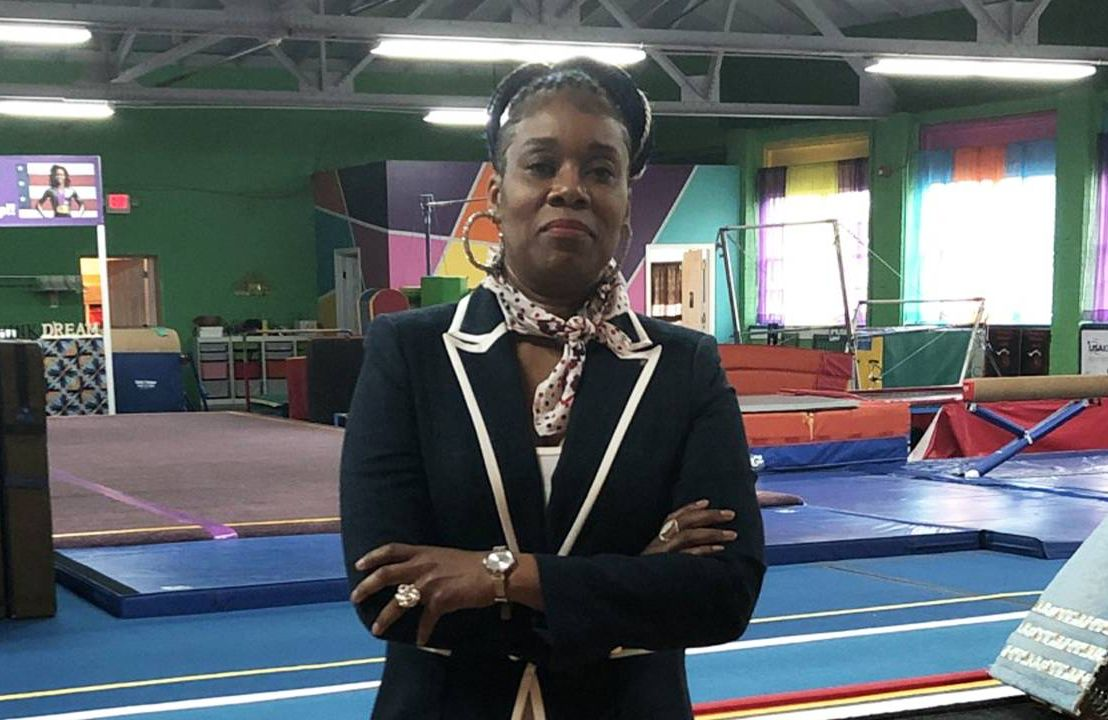 Middle aged woman wearing blazer standing inside a gym. Small business, Next Avenue