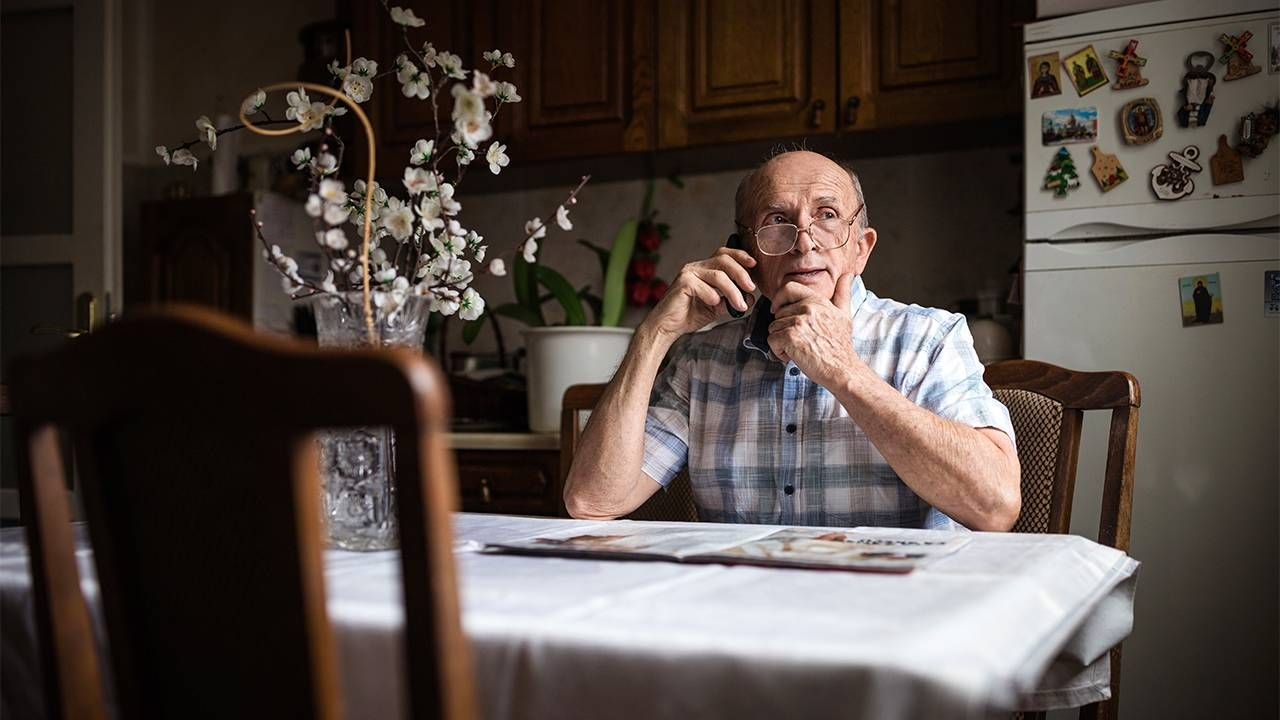 Older adult man talking on the phone sitting at the kitchen table. Medical, hospital, Next Avenue