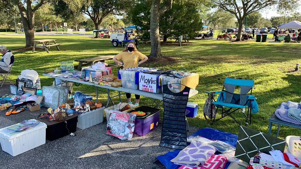 An outdoor yard sale with a young adult standing behind a table full of items. Next Avenue