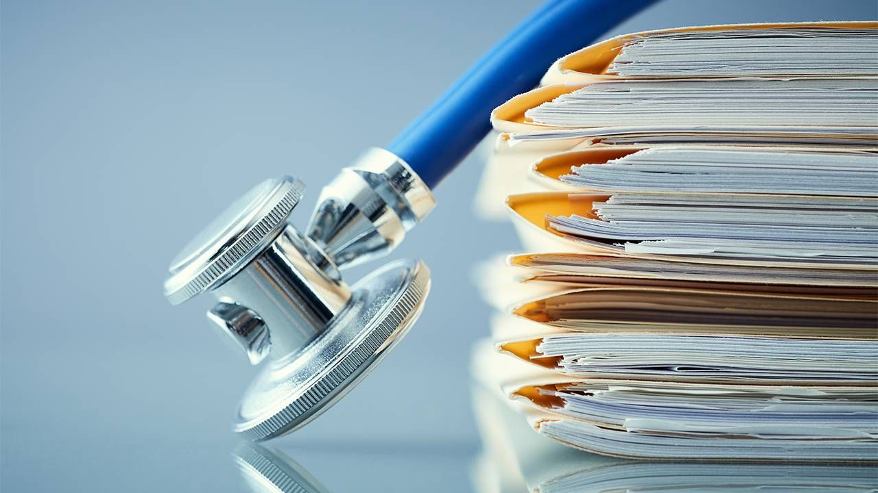 a stethoscope on top of a pile of medical records, health, Next Avenue