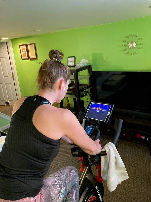 Woman exercising at home on an exercise bike, running, Next Avenue