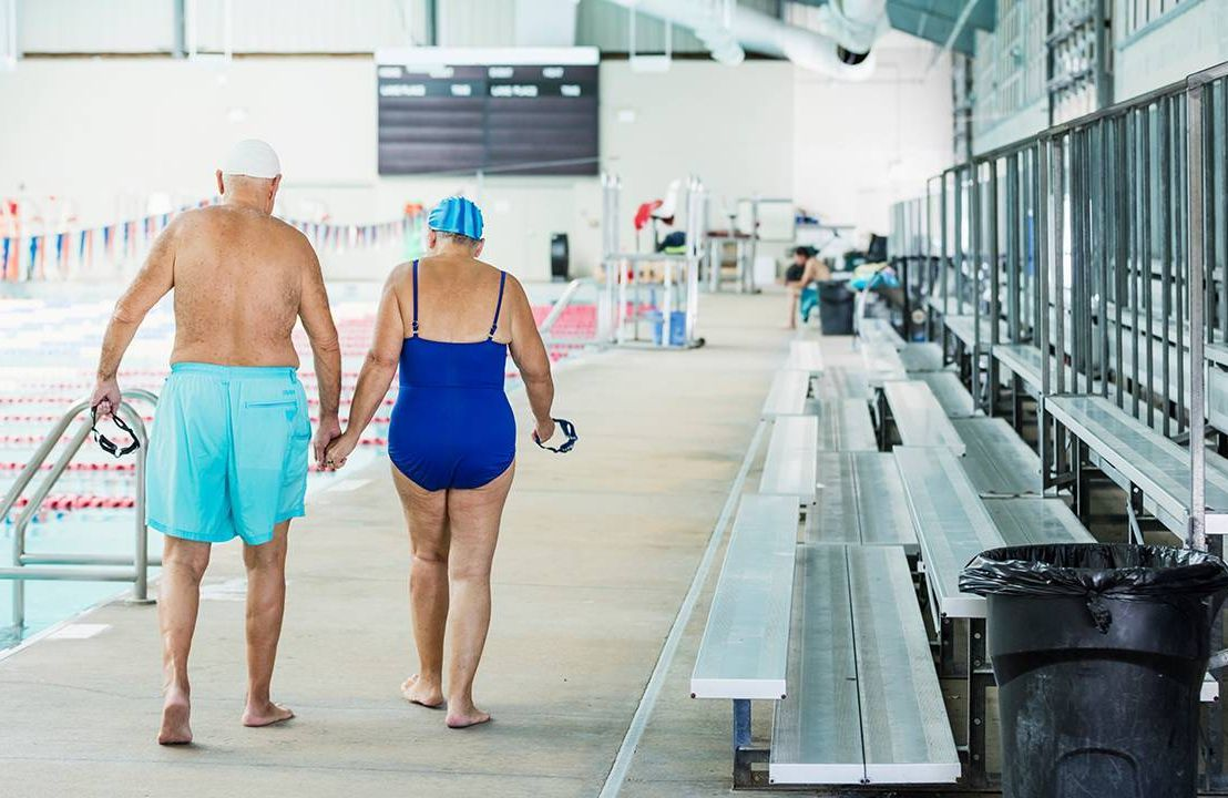 Older couple wearing swimsuits walking over to swim laps in the pool, exercise, running, Next Avenue