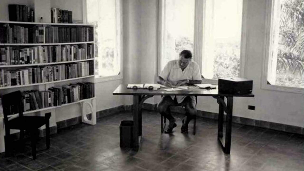 Old photo of Hemingway sitting at his desk, Next Avenue