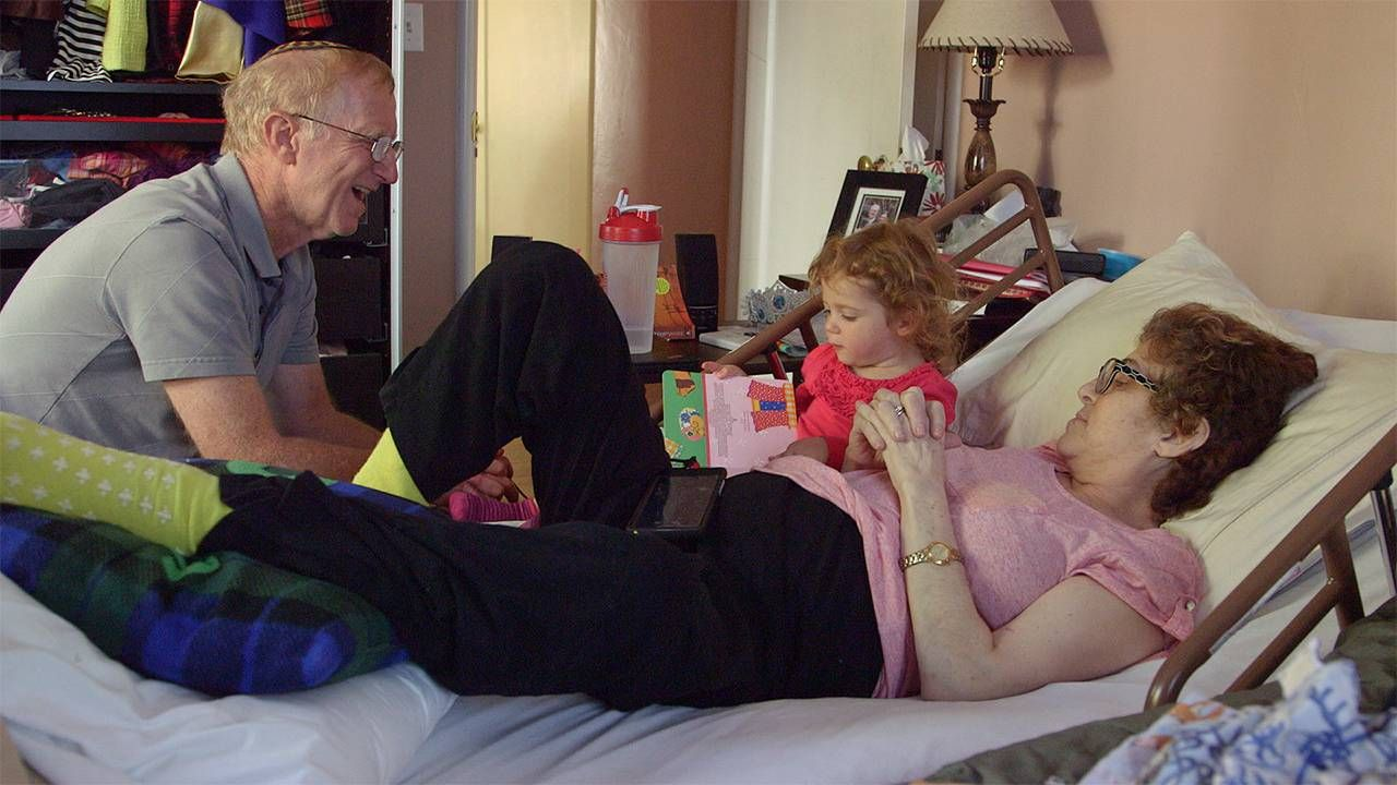 Toddler sitting on bed with older woman who is laying down next to an older man, caregiver, caregiving, Next Avenue