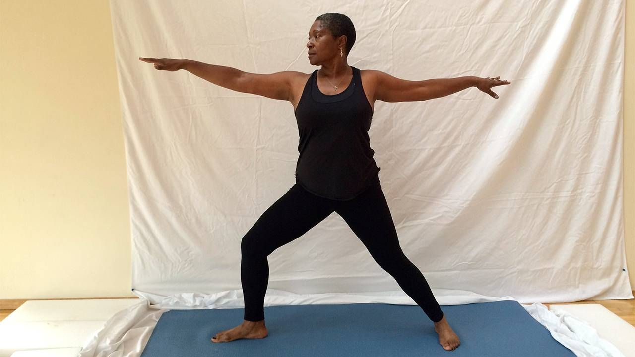 Middle aged woman standing in warrior pose, yoga, Next Avenue