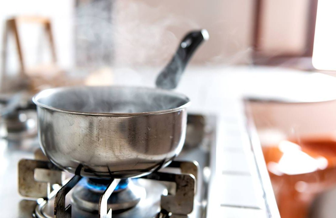A pot of boiling broth on a stove in a sunny kitchen, caregiver, Next Avenue