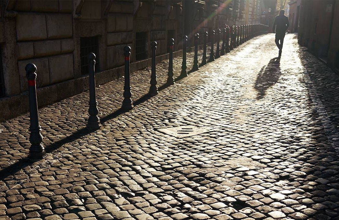 A shadow of a person walking toward the light down a cobblestone street. Remission, cancer, Next Avenue