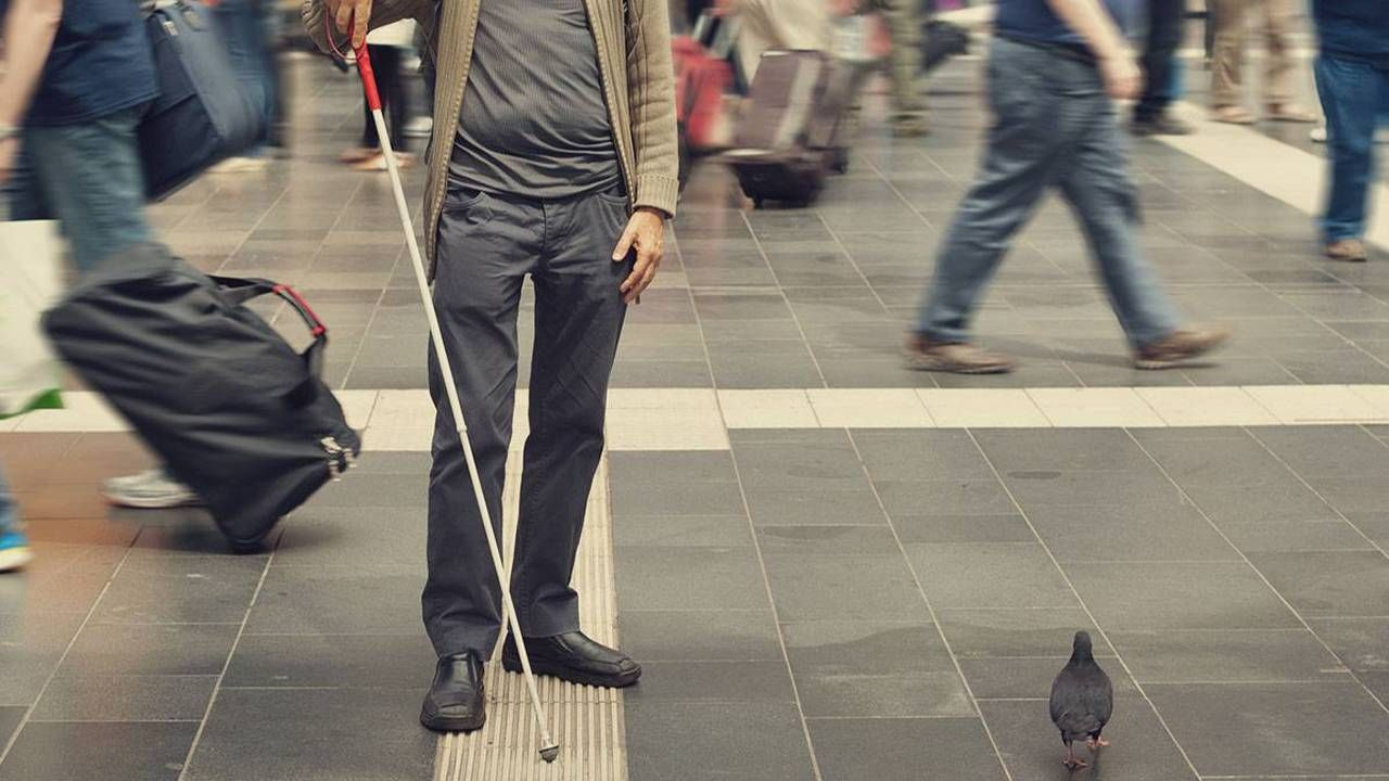 A blind man walking through an intersection using a walking stick.