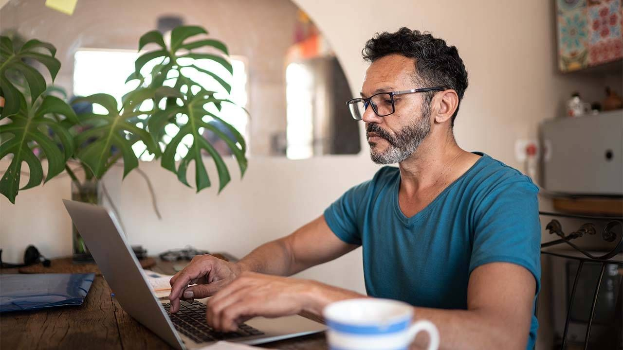 An older man with a greying beard looking for a job on his laptop at home. New job, onboarding, Next Avenue