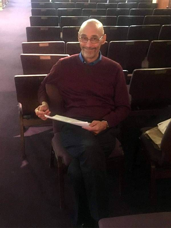 An older man sitting alone in a theater smiling. Drama, Actors, Next Avenue