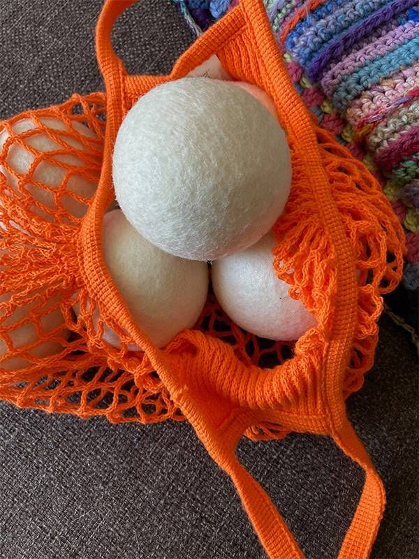 Close up of 5 wool dryer balls in an orange netted bag. Purchases, Next Avenue