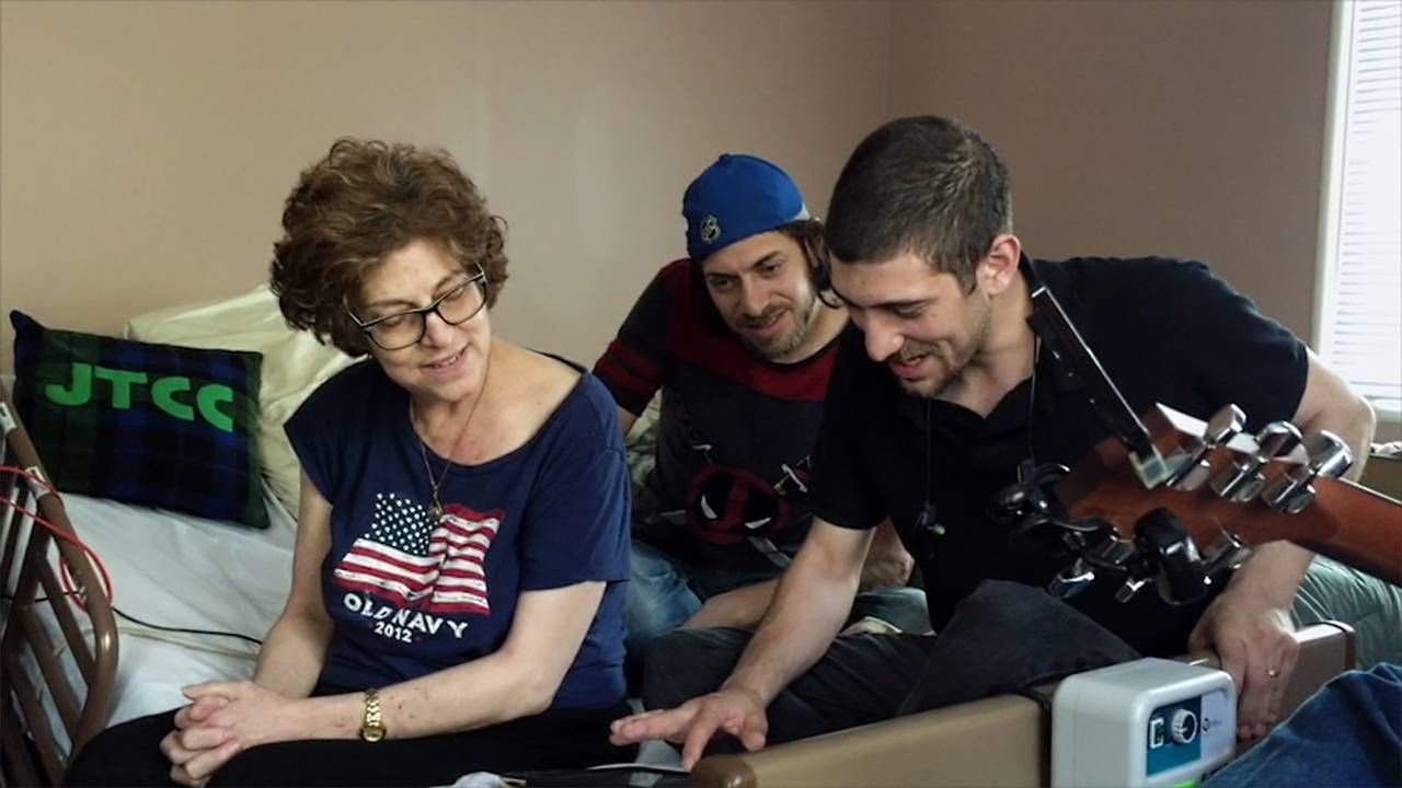 A mother and her two sons sitting on a bed playing the guitar, caregiver, caregiving, Next Avenue