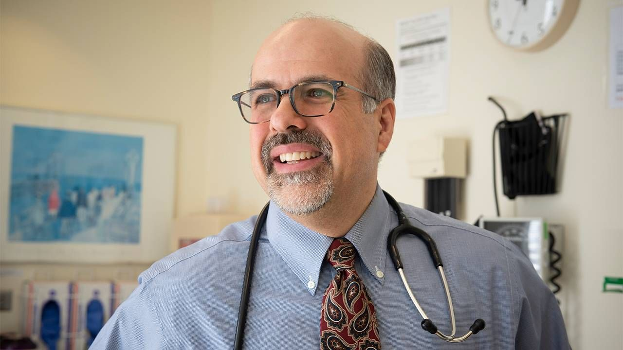 Photo of poet Dr. Campo wearing a stethoscope around his neck in his office. Poets, poetry, Next Avenue