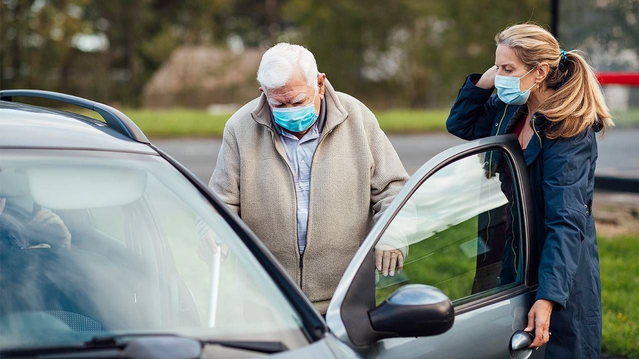 Caregiver and daughter helping her dad into the car. Family caregiver, paid family leave, Next Avenue