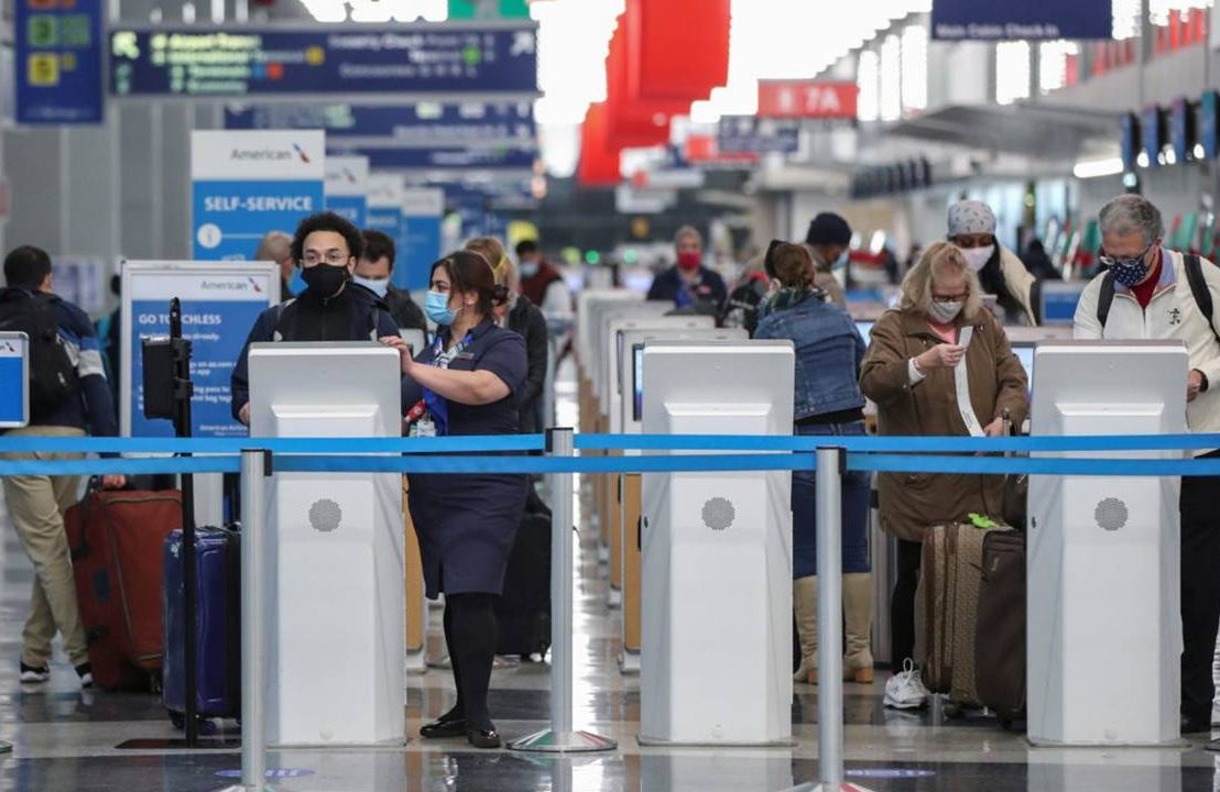 People standing at a ticketing kiosk in an airport wearing face masks. Travel, vaccinated travel, Next Avenue